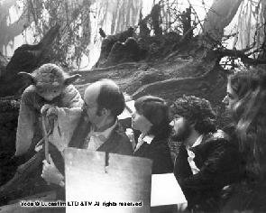 Black and white photograph of Yoda with puppeteers and designers alongside